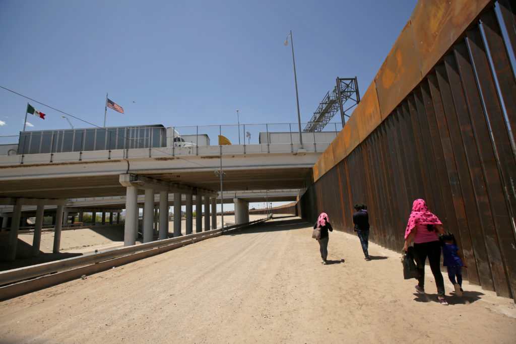 A group of Central American migrants walk next to the U.S.-Mexico border fence after they crossed the borderline in El Pas...