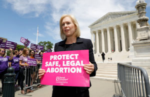 Democratic 2020 U.S. presidential candidate and U.S. Senator Kirsten Gillibrand (D-NY) holds a protest sign in front of a crowd of abortion rights demonstrators during a rally outside the U.S. Supreme Court in Washington, on May 21, 2019. Photo by Kevin Lamarque/Reuters