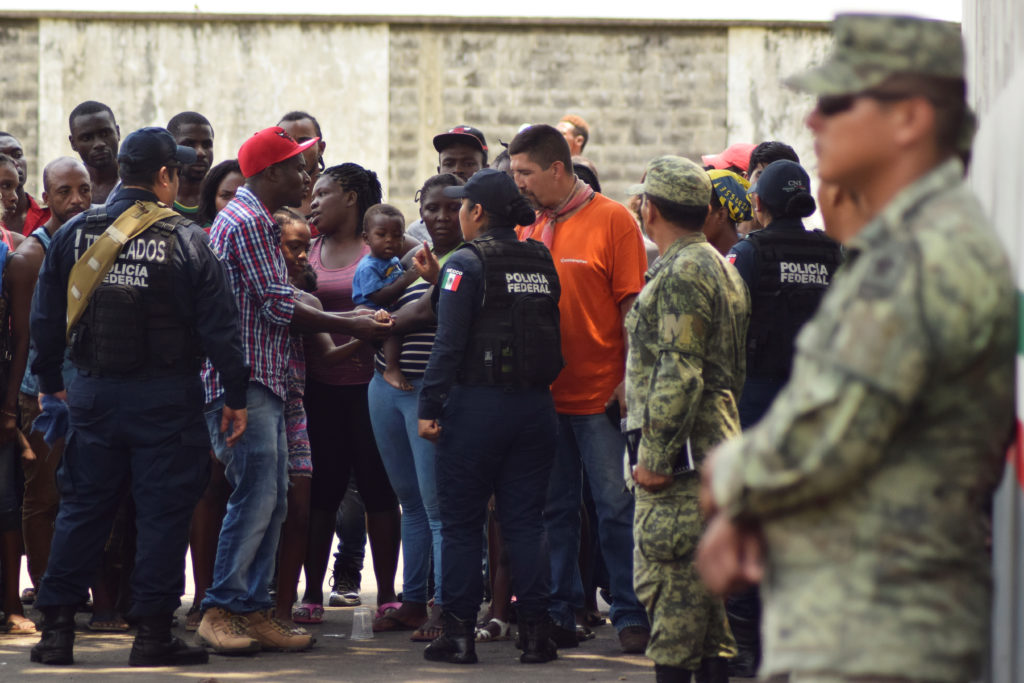Migrants talk to police officers as soldiers, assigned to the newly created National Guard, keep watch outside the Siglo XXI immigrant detention center as part of the security measures by the federal government, in Tapachula, Mexico May 23, 2019. Photo by Jose Torres/Reuters