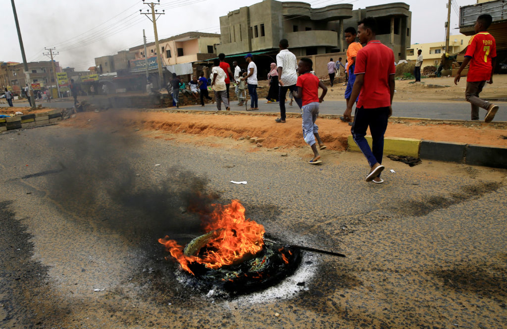 Sudanese protesters walk past burning tires used to erect a barricade on a street, demanding that the country's Transitional Military Council handover power to civilians, in Khartoum, Sudan on June 4, 2019. Photo via Reuters
