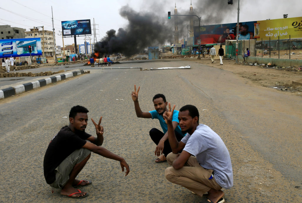 Sudanese protesters gesture as they sit-in near a barricade on a street, demanding that the country's Transitional Militar...