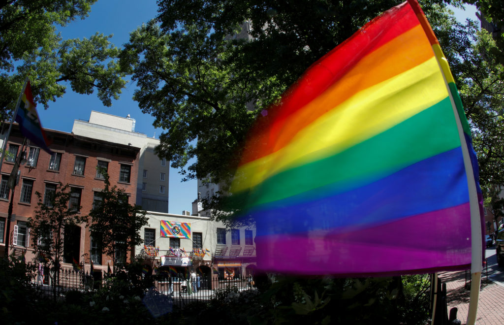 A rainbow flag waves in the wind at the Stonewall National Monument…