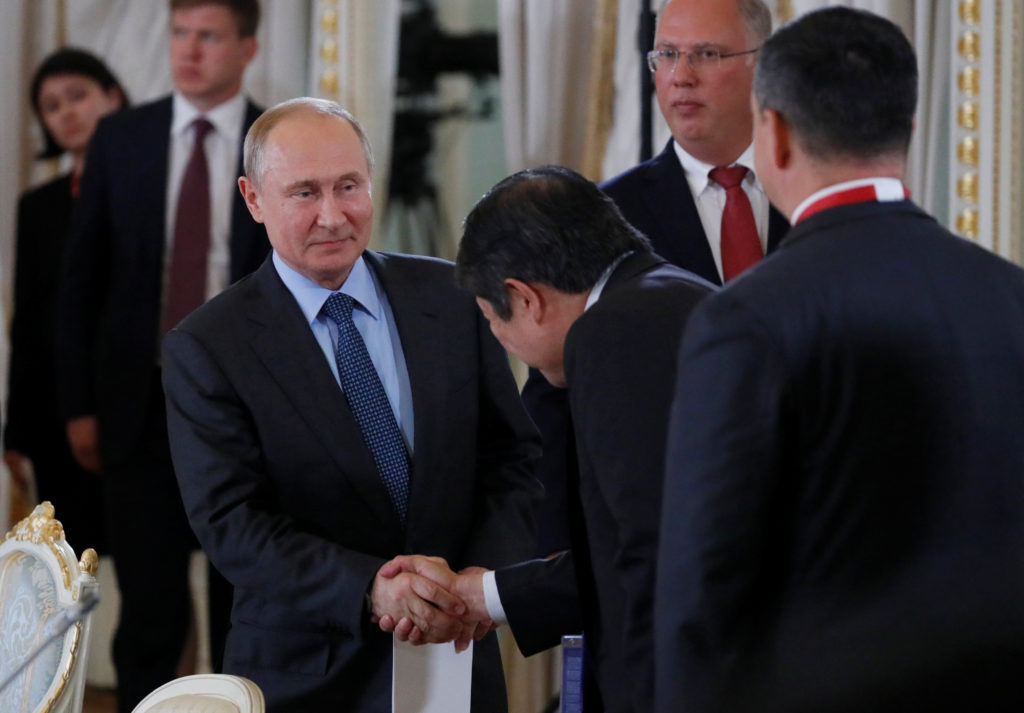 Russian President Vladimir Putin shakes hands with a participant at…