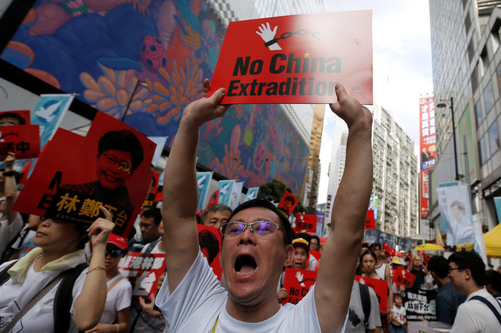 A demonstrator holds up a sign during a protest to demand authorities scrap a proposed extradition bill with China, in Hon...