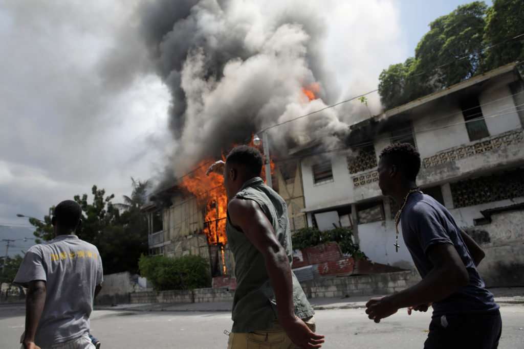 Protesters walk past a burning building during a demonstration called by opposition parties and civil society to protest a...