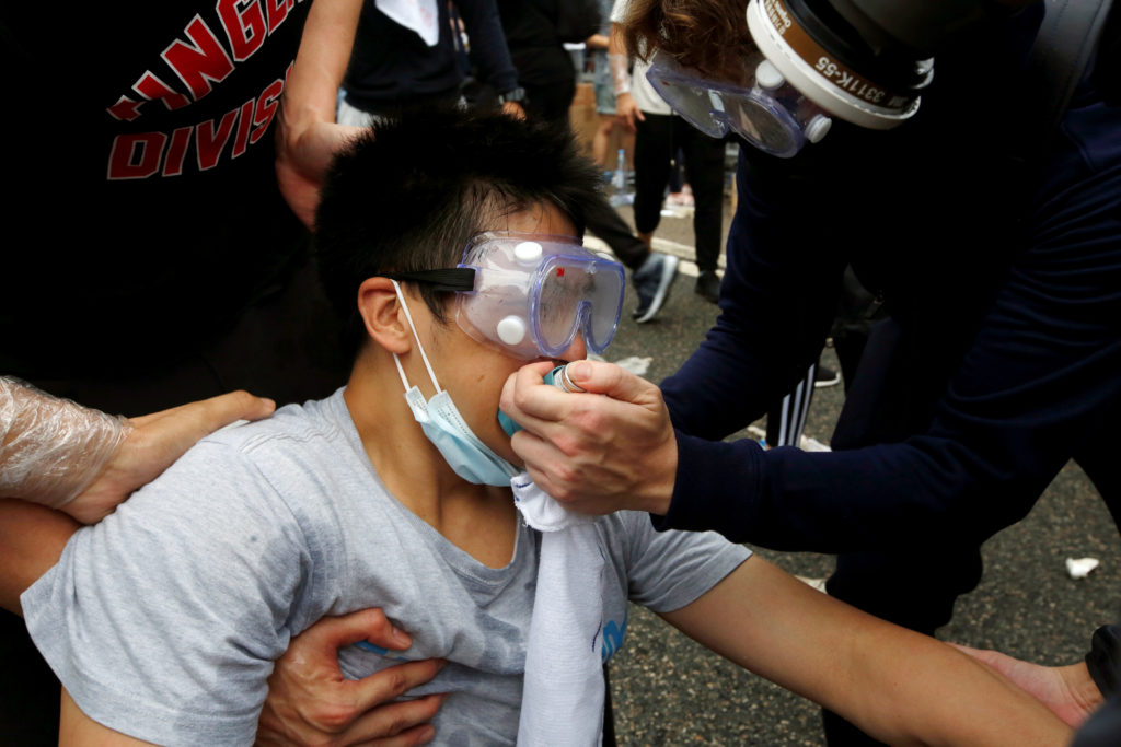 Protesters help a man during a demonstration against a proposed extradition bill where tear gas was fired, in Hong Kong, on June 12, 2019. Photo by James Pomfret/Reuters