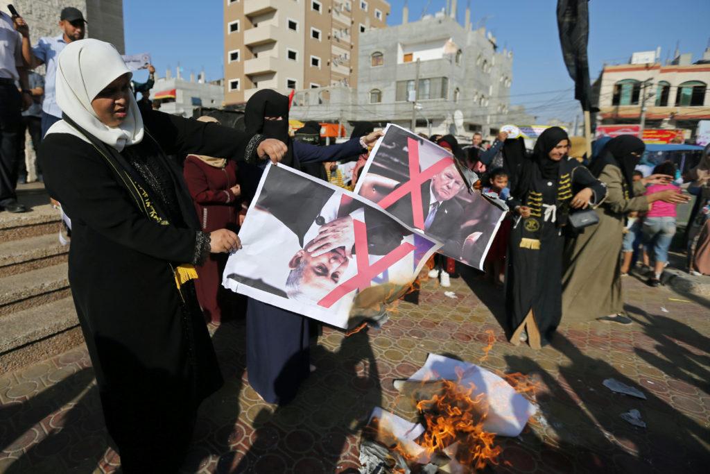 Palestinian women burn posters depicting U.S. President Donald Trump and Israeli Prime Minister Benjamin Netanyahu during ...