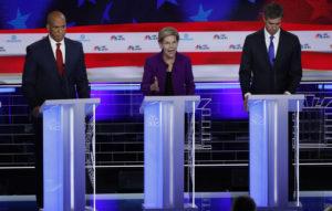 U.S. Senator Cory Booker and former U.S. Rep. Beto O'Rourke listen as U.S. Senator Elizabeth Warren speaks at the first U.S. 2020 presidential election Democratic candidates debate in Miami, Florida, U.S., June 26, 2019. REUTERS/Mike Segar