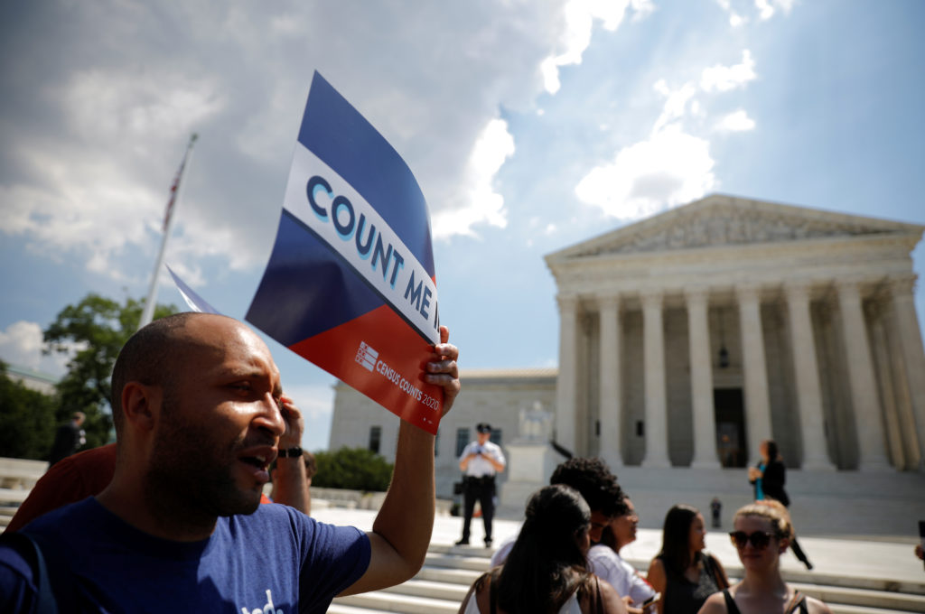 A protester holds a sign outside the U.S. Supreme Court, which ruled that President Donald Trump's administration did not ...