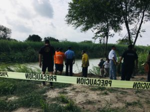 Authorities stand behind yellow warning tape along the Rio Grande bank where the bodies of Salvadoran migrant Oscar Alberto Martínez Ramírez and his nearly 2-year-old daughter Valeria were found, in Matamoros, Mexico, Monday, June 24, 2019, after they drowned trying to cross the river to Brownsville, Texas. Martinez' wife, Tania told Mexican authorities she watched her husband and child disappear in the strong current. AP Photo/Julia Le Duc