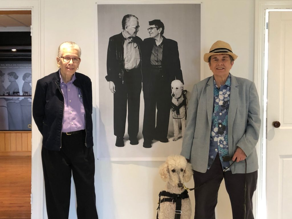 When someone during the early days of the LGBTQ rights movement that they wanted the right to same-sex marriage, lesbian activist Karla Jay (right) and others thought the idea was too far fetched. Today, she is married to her wife, Karen Kerner (left). The couple and their dog Duchess stand in front of a picture of themselves by photographer Collier Schorr at The Alice Austen House. Photo courtesy of Karla Jay