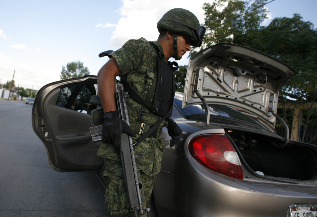 A soldier searches a vehicle for drugs and weapons next to a crime scene where a man was gunned down in the border city of Ciudad Juarez September 8, 2009. A crackdown by thousands of troops and federal police has been unable to curb turf wars between rival cartels. More than 13,000 people have died in drug violence since Mexican president Felipe Calderon took office in late 2006. REUTERS/Tomas Bravo (MEXICO CONFLICT CRIME LAW SOCIETY MILITARY) - GM1E5990TM101