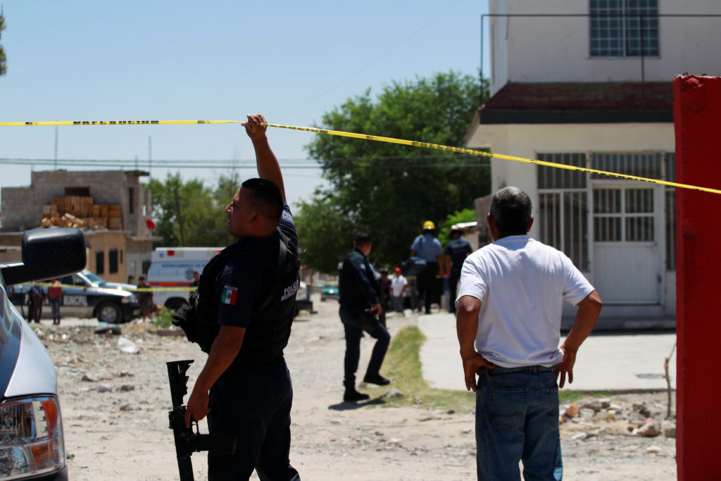 A policeman holds up a police cordon as a relative reacts at a crime scene where several people were gunned down by unknown assailants in Ciudad Juarez, Mexico June 23, 2018. REUTERS/Jose Luis Gonzalez - RC144CC58660
