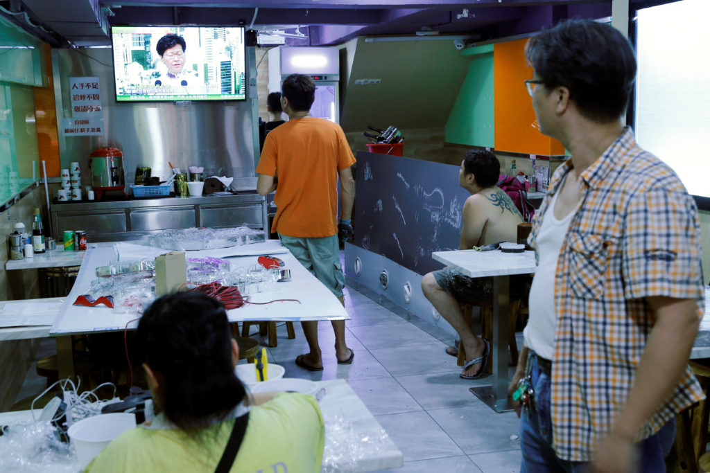 People watch a TV broadcast of news conference of Hong Kong Chief Executive Carrie Lam inside a restaurant in Hong Kong, China, June 15, 2019.  Photo by Thomas Peter/Reuters