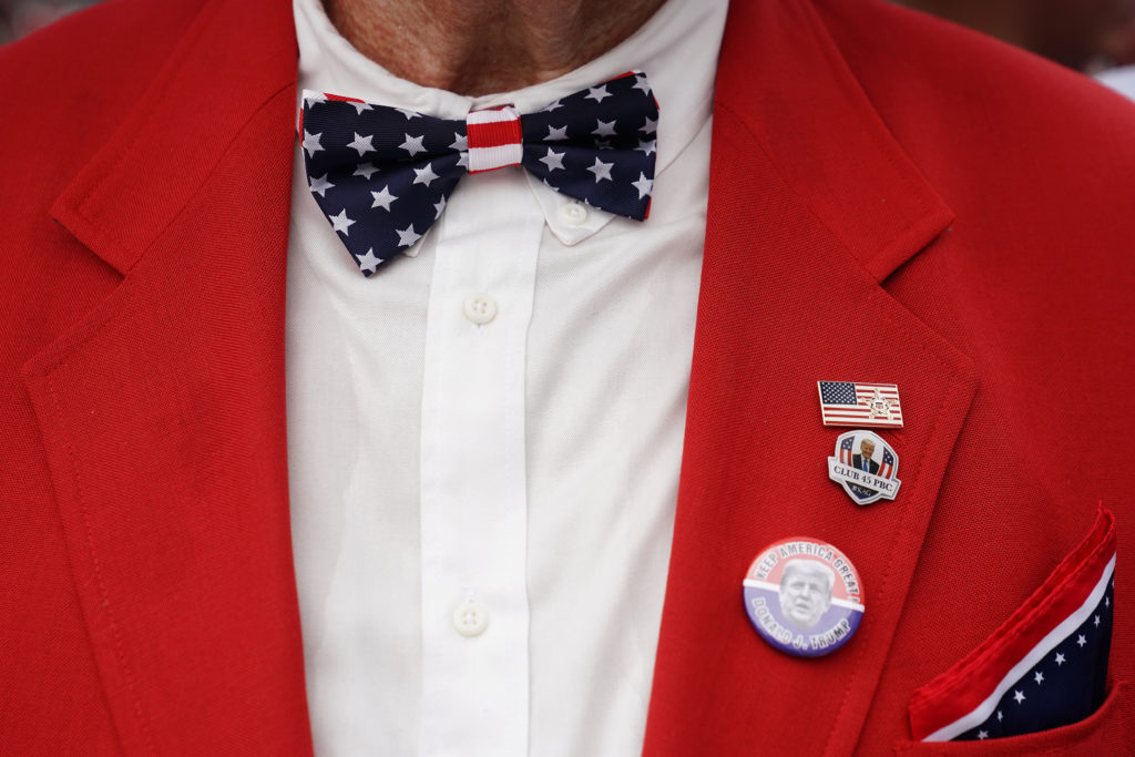 A man with a U.S flag bowtie poses for a photo at a rally for U.S. President Donald Trump at the Amway Center in Orlando, Florida, U.S., June 18, 2019. REUTERS/Carlo Allegri - RC12AC102550