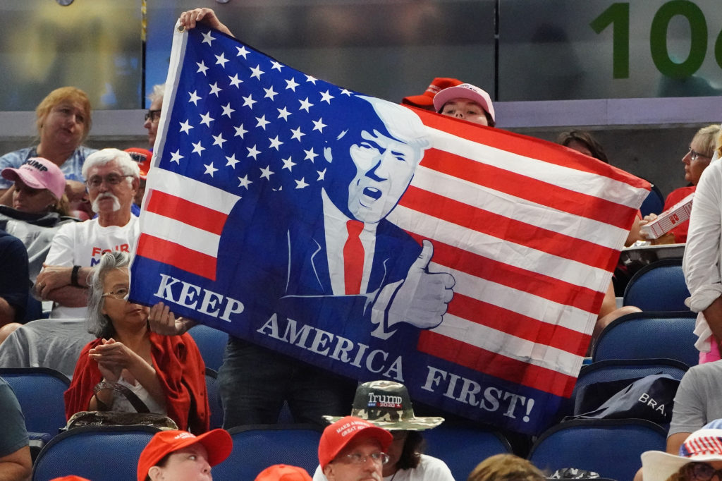 People sit in the stands with a flag before a rally for U.S. President Donald Trump at the Amway Center in Orlando, Florida, U.S., June 18, 2019. REUTERS/Carlo Allegri - RC112AA187D0