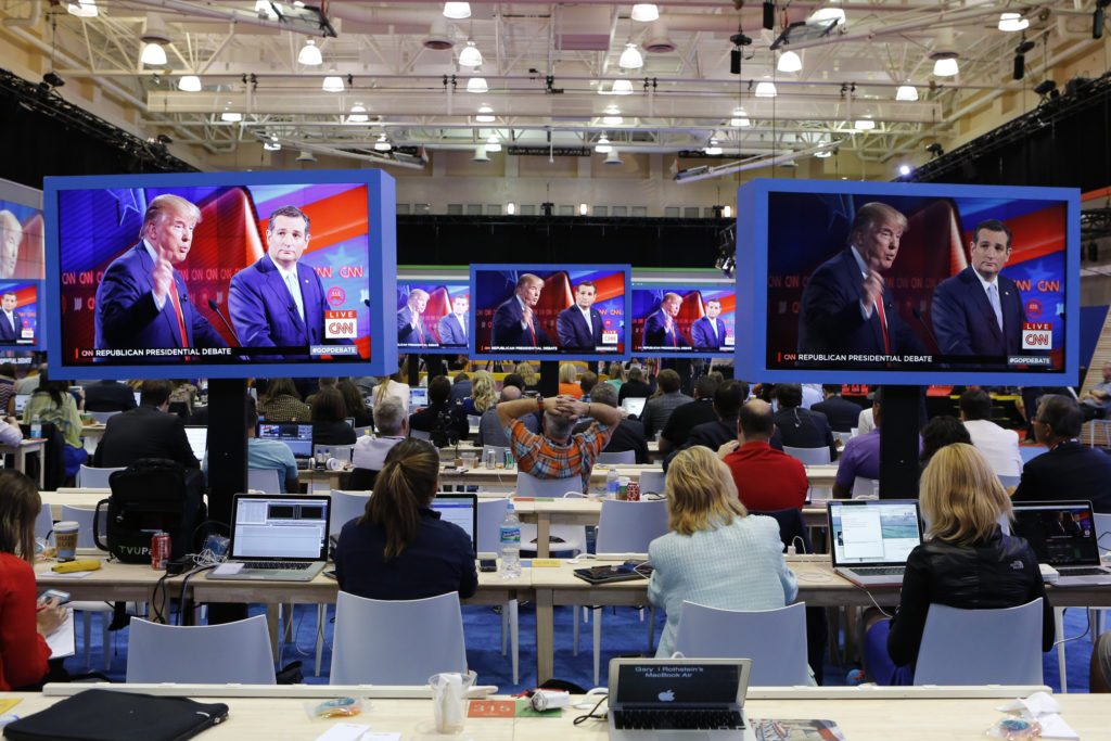 Journalists watch Republican U.S. presidential candidates Donald Trump (L) and Ted Cruz debate on large video monitors in the media filing center during the Republican U.S. presidential candidates debate sponsored by CNN at the University of Miami in Miami, Florida March 10, 2016. REUTERS/Joe Skipper - HP1EC3B0B6U00