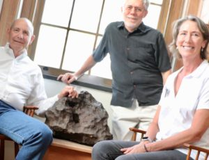 Drew Barringer (left), owner of Arizona meteor crater, his wife, Clare Schneider, and author William Herbst in the Van Vleck Observatory Library of Wesleyan University, where an iron meteorite from the crater is on display. Photo by W. Herbst