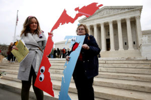 Demonstrators rally with cut-outs of congressional districts in front of the Supreme court before oral arguments on Benisek v. Lamone, a redistricting case on whether Democratic lawmakers in Maryland unlawfully drew a congressional district in a way that would prevent a Republican candidate from winning, in Washington, U.S., March 28, 2018. Photo by REUTERS/Joshua Roberts