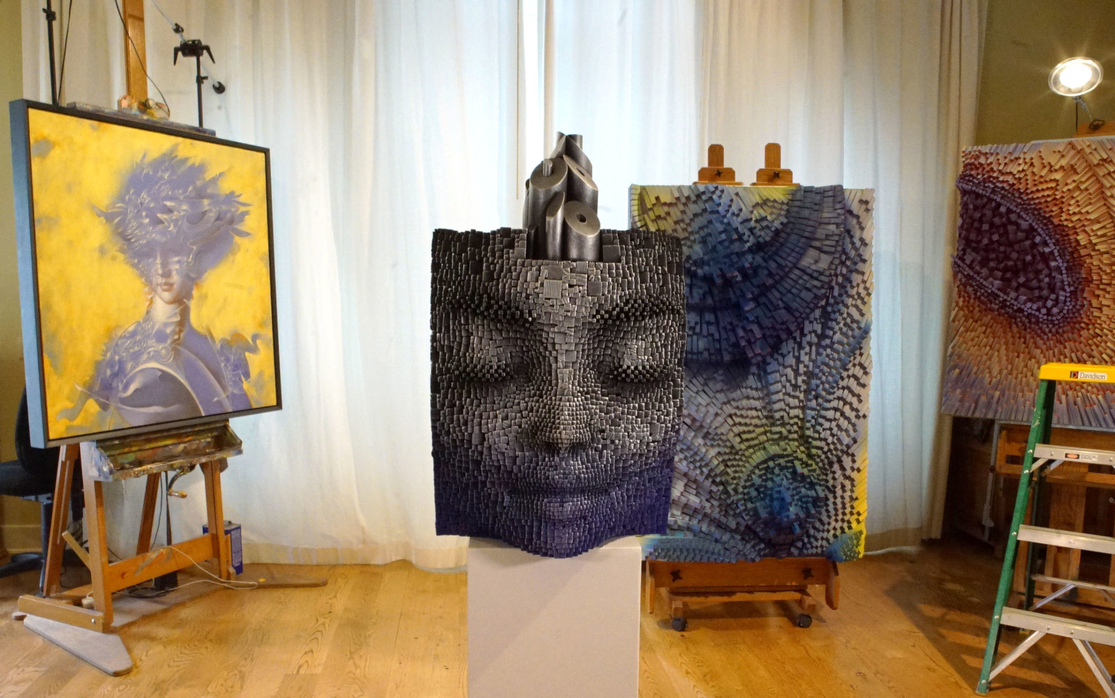 One of Bruvel's face sculptures next to the mixed media artist's other works. Photo by Joshua Barajas/PBS NewsHour