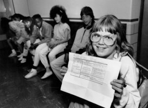 Sixth grader Ginger Taylor shows proof of Immunization against the measles in 1989. Photo By Glen Martin/The Denver Post via Getty Images