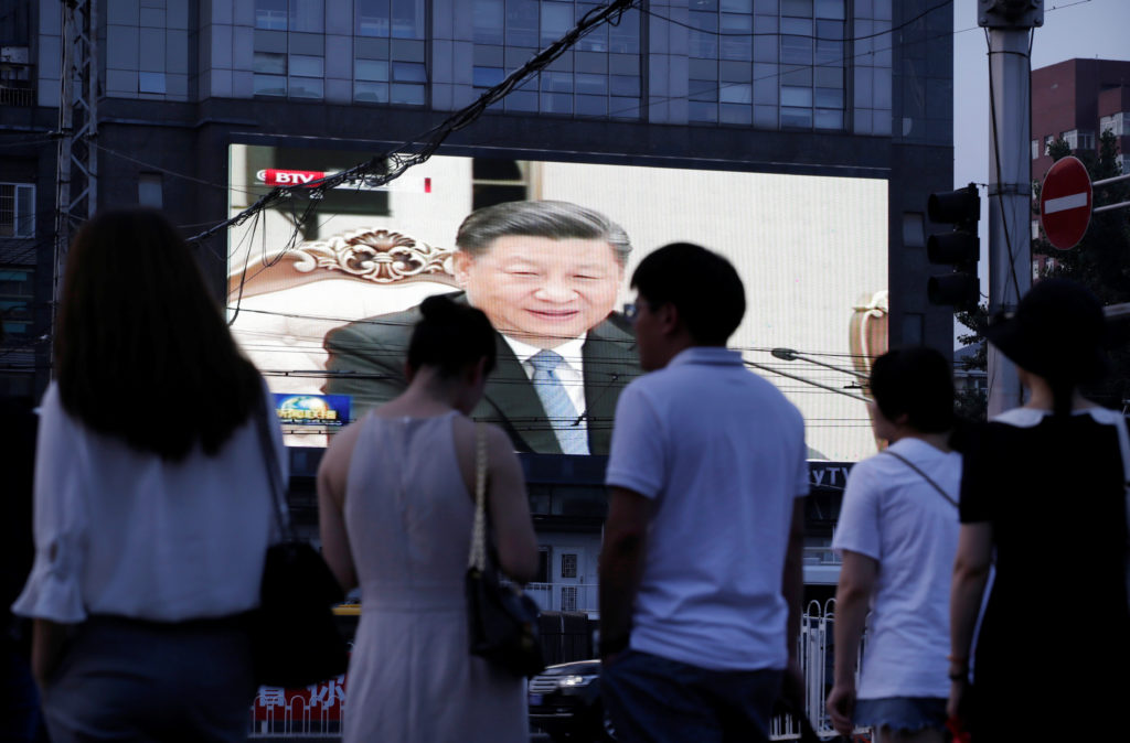 People wait to cross a street as a  television screen shows Chinese state media CCTV's footage of Chinese President Xi Jinping's meeting with North Korean leader Kim Jong Un (not on the screen) in Pyongyang, in Beijing, China June 20, 2019. REUTERS/Jason Lee