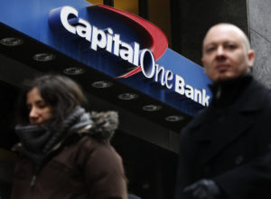 People walk past a Capital One banking center in New York's financial district January 17, 2013. Capital One Financial Corp's fourth-quarter profit missed analysts' expectations as the company set aside more money to cover defaults on its credit cards, sending its shares down 7 percent after the bell. Photo by REUTERS/Brendan McDermid