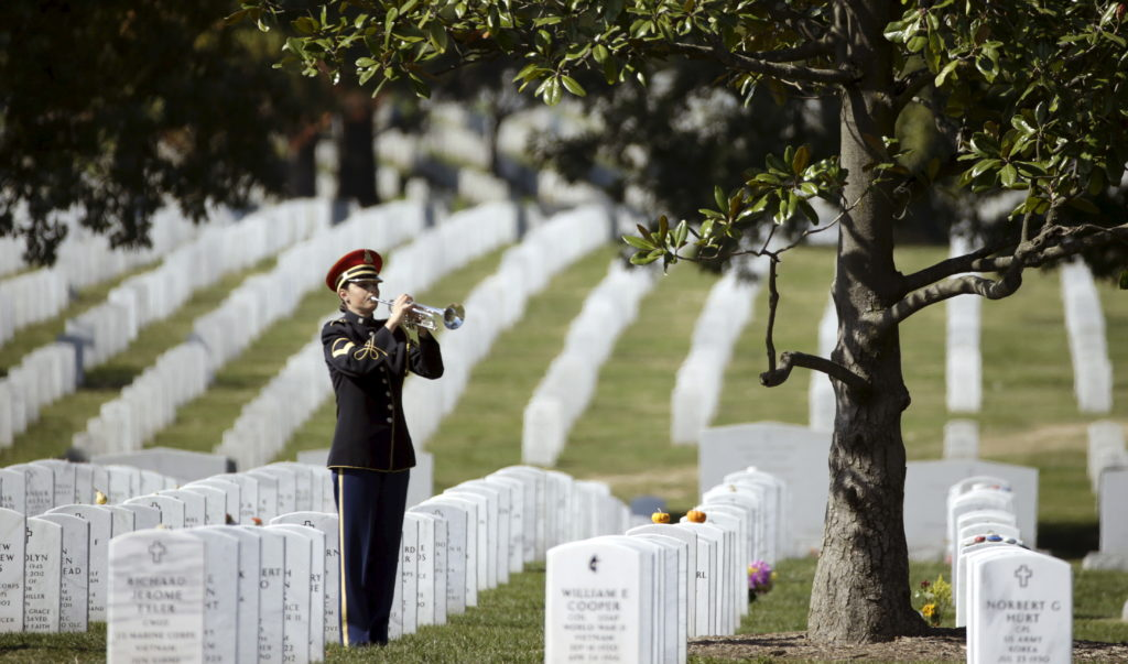 "A bugler plays ""Taps"" during a burial service at Arlington National Cemetery. Photo by Gary Cameron/Reuters"