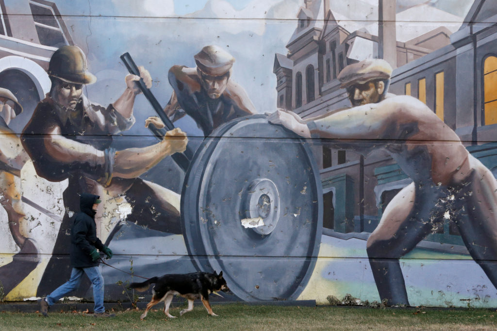 A man walks his dog past a mural depicting factory workers in the h…