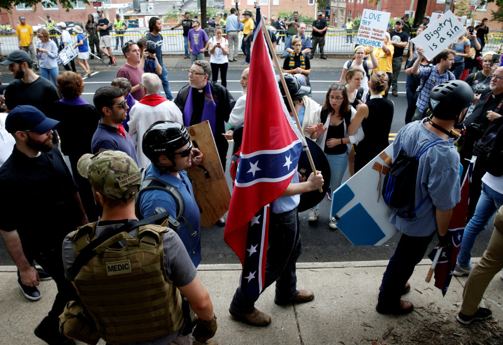 A white nationalist carries the Confederate flag as he walks past counter demonstrators in Charlottesville, Virginia, U.S., August 12, 2017. Photo by: Joshua Roberts/Reuters