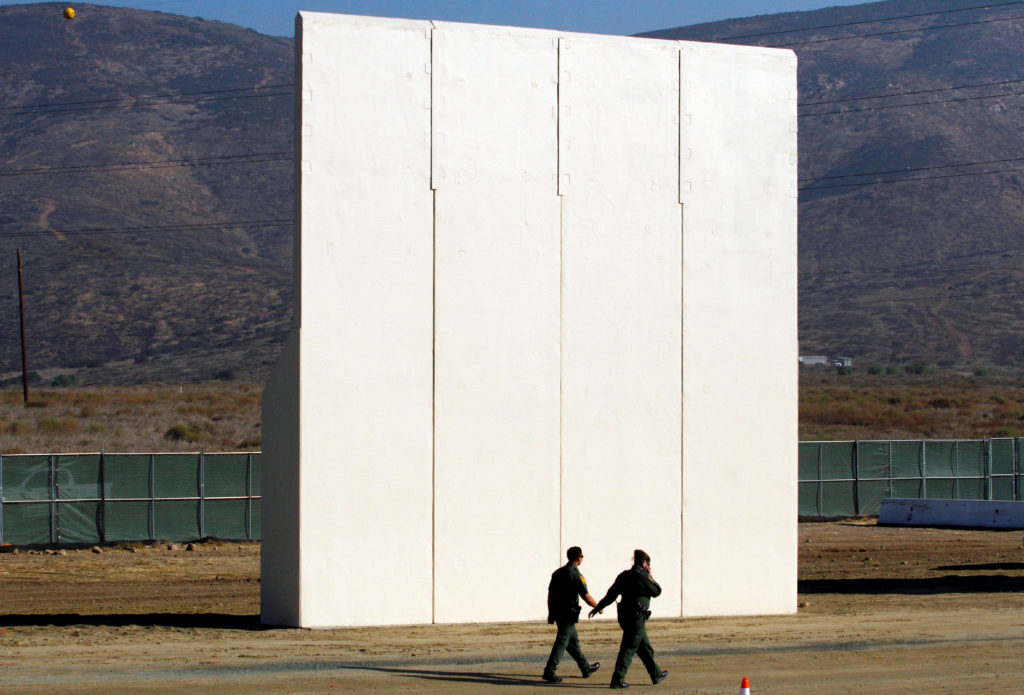 U.S. border patrol officers walk near a prototype for U.S. President Donald Trump's border wall with Mexico, in this pictu...