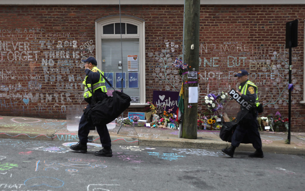 "Law enforcement walks past a memorial to Heather Heyer ahead of the one year anniversary of 2017 Charlottesville ""Unite the Right"" protests, in Charlottesville, Virginia, on August 11, 2018. Photo by Jim Urquhart/Reuters"