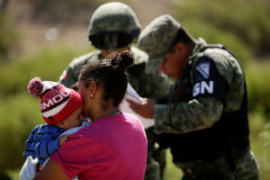 A Honduran migrant with her child are stopped by members of the Mexican National Guard in Anapra, on the outskirts of Ciudad Juarez, Mexico on June 28, 2019. Photo by Jose Luis Gonzalez/Reuters