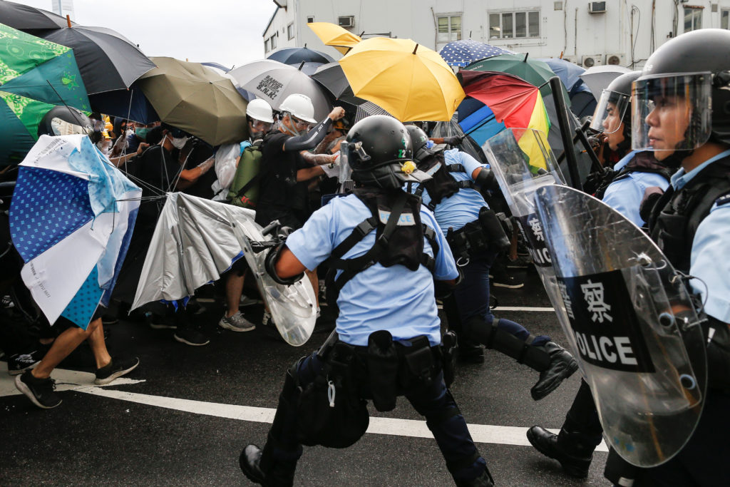 Police try to disperse protesters near a flag raising ceremony for the anniversary of Hong Kong handover to China. Photo by Thomas Peter/Reuters