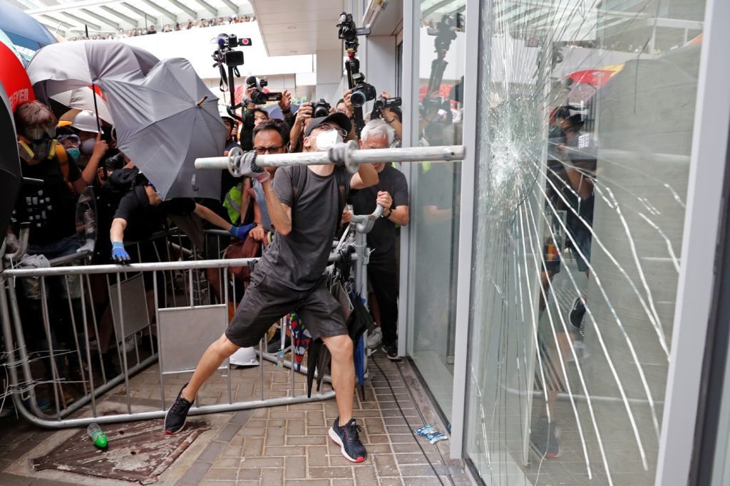 Protesters try to break into the Legislative Council building where riot police are seen, during the anniversary of Hong K...