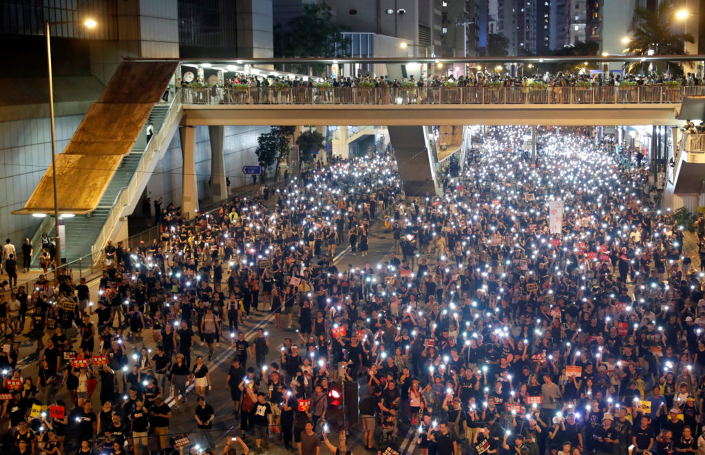 Anti-extradition bill protesters use the flashlights from their phones as they march during the anniversary of Hong Kong's handover to China. Photo taken on July 1, 2019. Photo by Tyrone Siu/Reuters