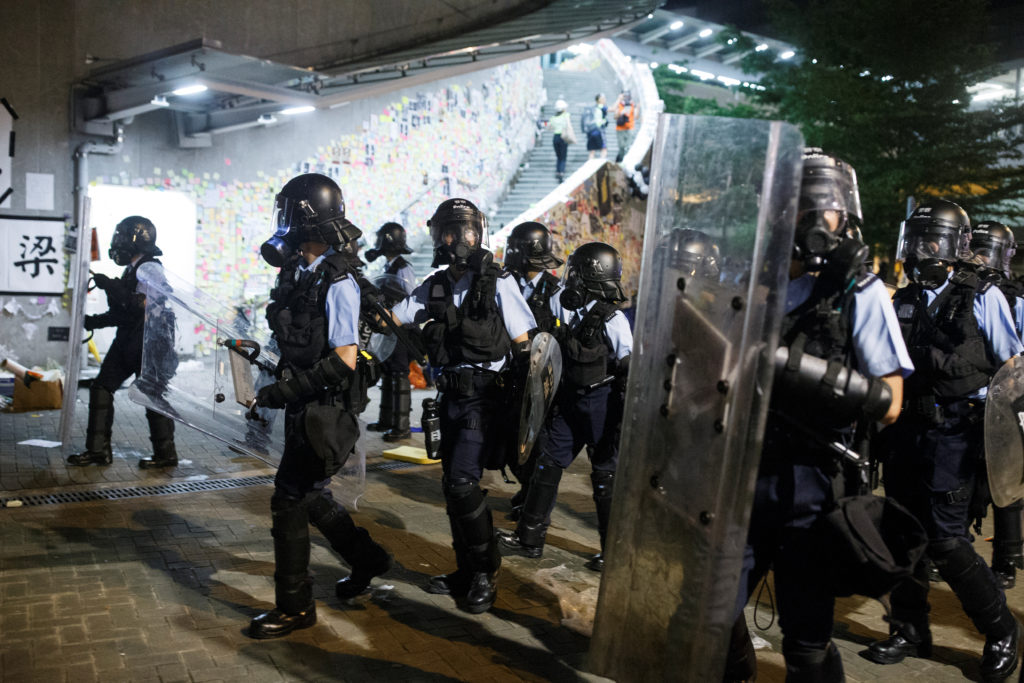 Riot police clear the streets outside the Legislative Council building, after protesters stormed the building on the anniv...