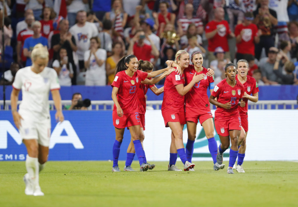 United States forward Alex Morgan (13) celebrates with teammates after scoring a goal against England in the first half of...