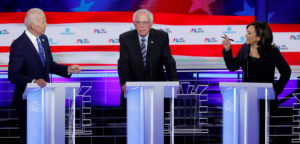 FILE PHOTO: Former Vice President Joe Biden and Senator Kamala Harris debate racial issues as Senator Bernie Sanders listens during the second night of the first U.S. Democratic presidential candidates 2020 election debate in Miami, Florida, on June 27, 2019. Photo by Mike Segar/Reuters
