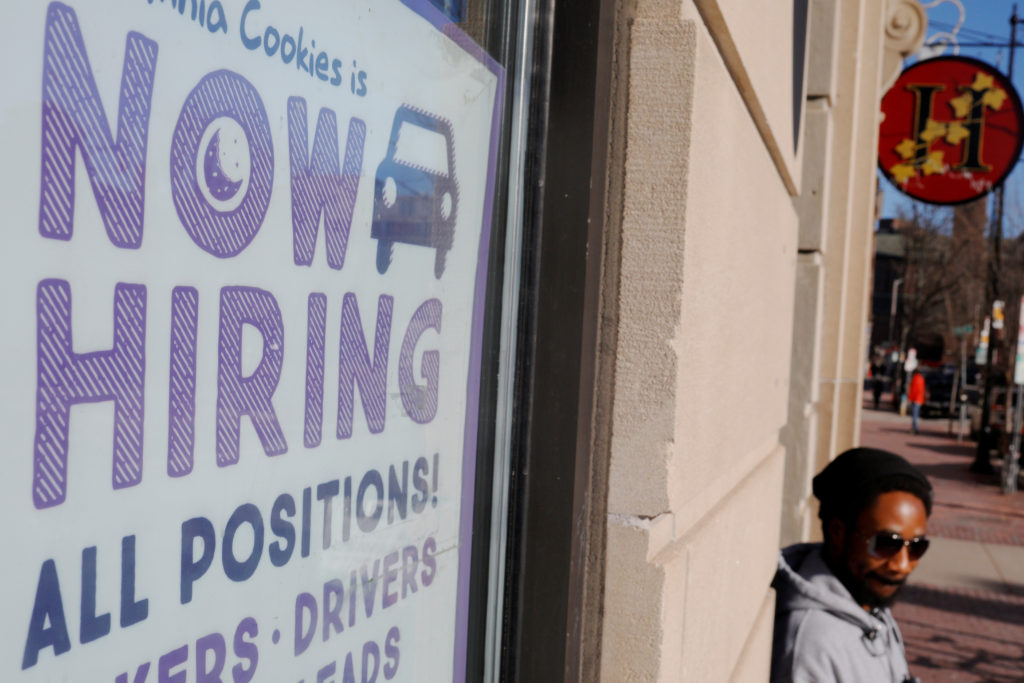 """A """"Now Hiring"""" sign sits in the window of Insomnia Cookies in Cambridge, Massachusetts, U.S., February 11, 2019. Photo by Brian Snyder/Reuters"""