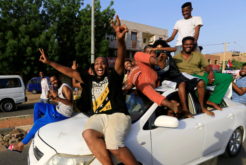 Sudanese people ride atop a car chanting slogans as they celebrate, after Sudan's ruling military council and a coalition ...