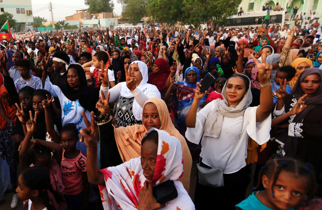 Sudanese people chant slogans as they celebrate, after Sudan's ruling military council and a coalition of opposition and p...