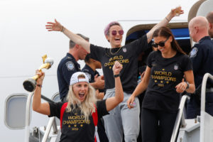 U.S. soccer players Julie Ertz (left), Megan Rapinoe (center) and Alex Morgan celebrate as they exit the plane with the Trophy for the FIFA Women's World Cup while the U.S team arrive at the Newark International Airport, in Newark, New Jersey, on July 08, 2019. Photo by Eduardo Munoz/Reuters
