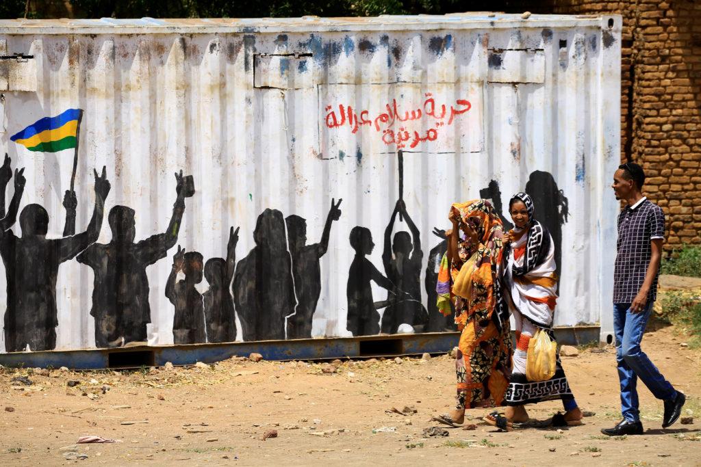"Civilians walk past graffiti reading in Arabic ""Freedom, Peace, Jus…"