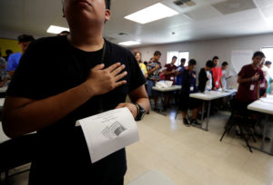 Immigrants say the Pledge of Allegiance in a writing class at the U.S. government's newest holding center for migrant children in Carrizo Springs, Texas, U.S. July 9, 2019. Following breakfast, children play soccer and then have classes held in trailers. Picture taken July 9, 2019. Photo by Eric Gay/Pool via REUTERS