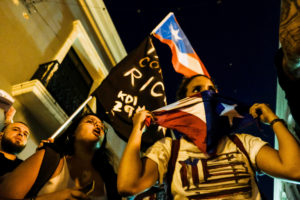 Demonstrators chant and wave Puerto Rican flags during the fourth day of protest calling for the resignation of Governor Ricardo Rossello in San Juan, Puerto Rico on July 16, 2019. Photo by Gabriella N. Baez/Reuters