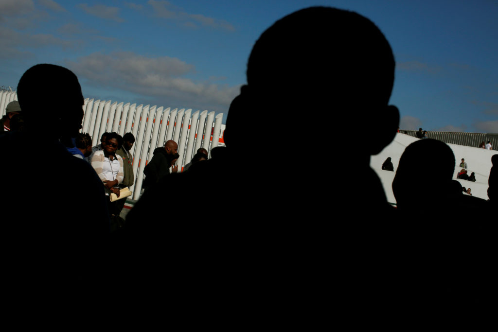 Migrants queue to apply for asylum in the United States, at El Chap…
