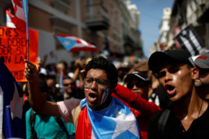 Men shout during ongoing protests calling for the resignation of Governor Ricardo Rossello in San Juan, Puerto Rico on July 20, 2019. Photo by Marco Bello/Reuters