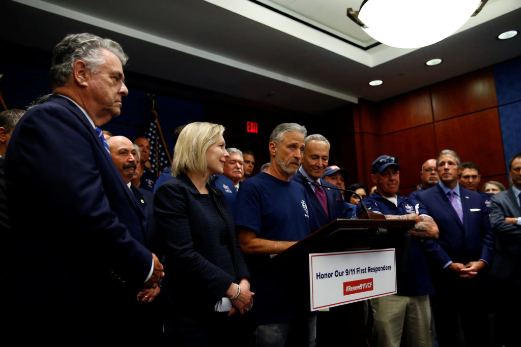 "Jon Stewart, former host of Comedy Central's ""The Daily Show"" joins Senate Democratic Leader Chuck Schumer (D-NY), 2020 Democratic presidential candidate Sen. Kirsten Gillibrand (D-NY), House Judiciary Chairman Jerrold Nadler (D-NY) and Peter King (R-NY) at a news conference following the Senate vote on the ""Never Forget the Heroes Act"" on Capitol Hill in Washington, on July 23, 2019. Photo by Eric Thayer/Reuters"