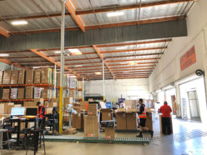 A worker walks passed boxes on a roller conveyor at NewAir's wareho…
